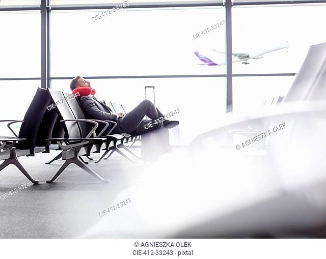 Businessman resting with neck pillow in airport departure area