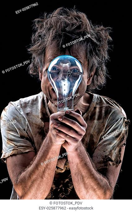 Portrait of burnt man with light bulb over black background