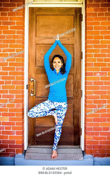 Hispanic woman practicing yoga in doorway