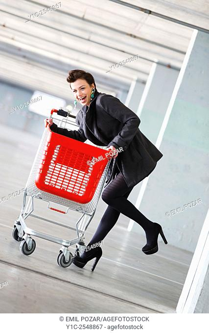 Young woman shopper with empty cart