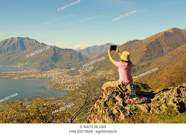 Woman Takes Pictures From Mountain Overlook in Ticino, Switzerland