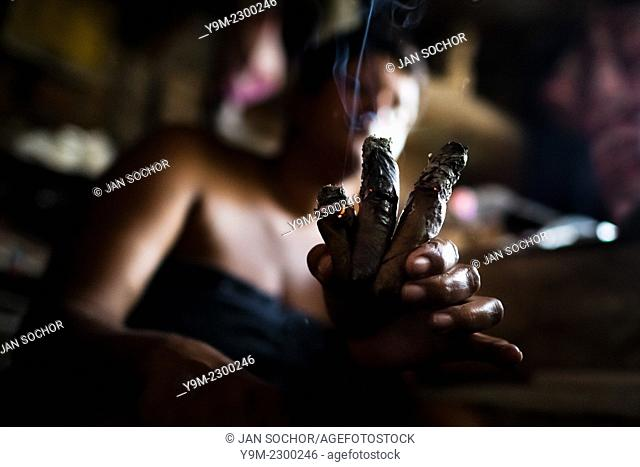 A Colombian woman shows three burning cigars while predicting the future from shapes shown on the tobacco leaves in a shaman's house in Cali, Colombia
