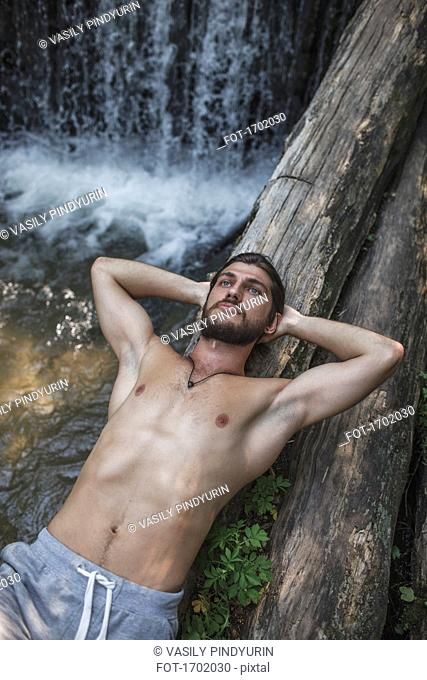 Thoughtful shirtless man lying on logs over waterfall at forest