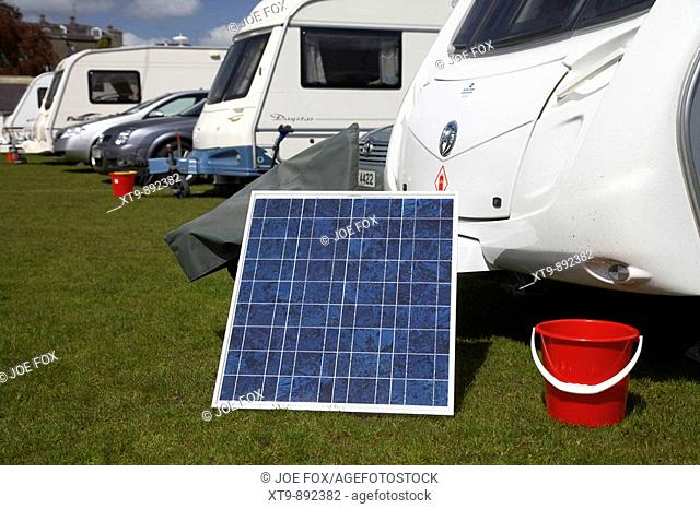solar power panel and red fire bucket outside caravan on a caravan site in county armagh northern ireland uk