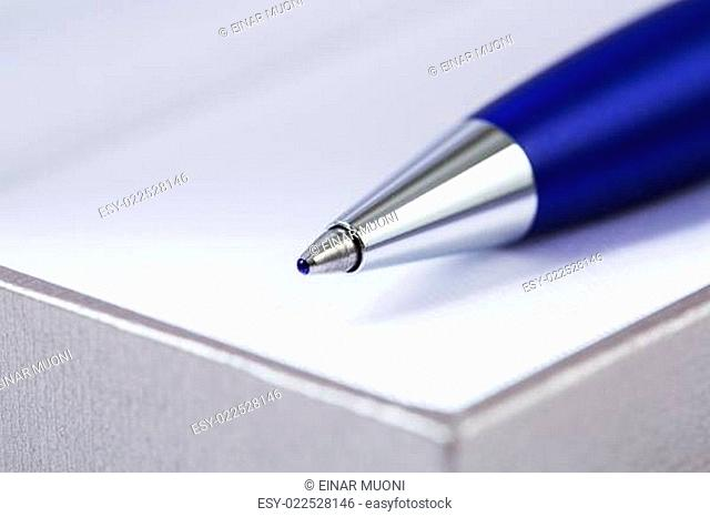 Zoomed pen head on block of papers