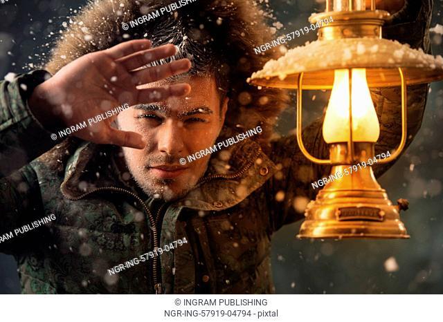 Brutal man walking under snowstorm at night lighting his way with lantern