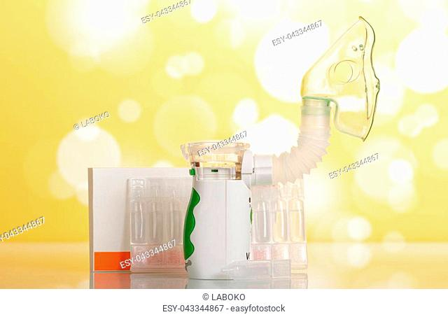 Electronic mesh nebulizer with pediatric mask, box of spare vials, on yellow background