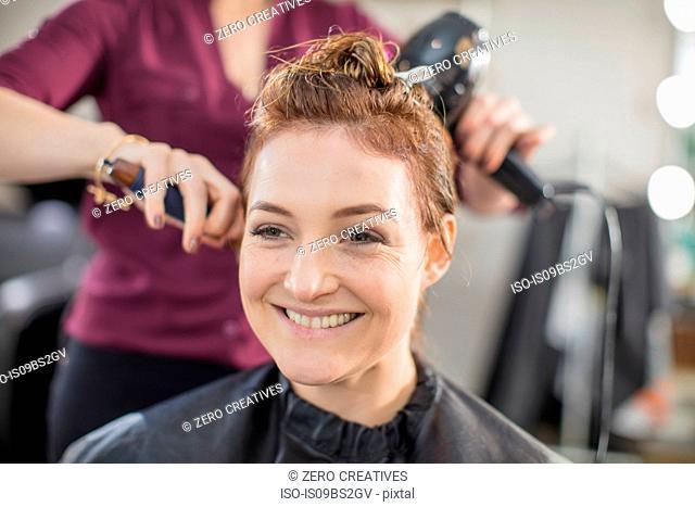 Hairdresser blow drying customer's hair in salon