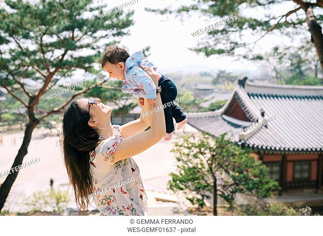 South Korea, Seoul, Happy mother and baby girl playing in Changdeokgung Palace and Huwon