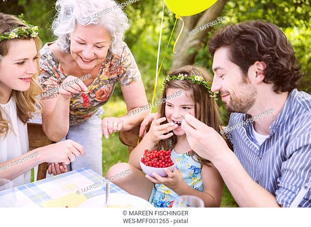 Family enjoying a bowl with redcurrants at table outside