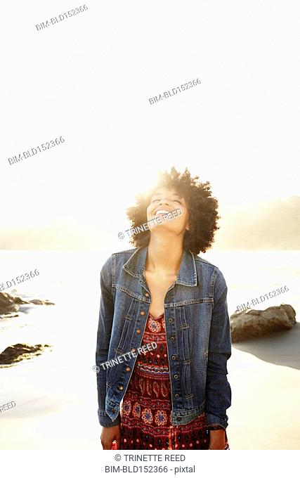 Back lit mixed race woman laughing