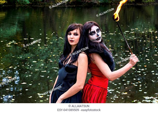 Two young brunettes women with makeup like a Halloween skull and Halloween witch makeup stands with a torch in a red and black dresses in front of the autumn...