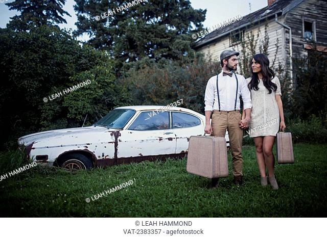A couple with vintage suitcases stand together outside a house with an old car; Edmonton, Alberta, Canada