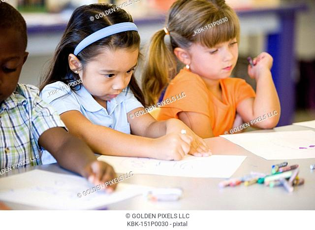 Girls drawing with crayons in an art class