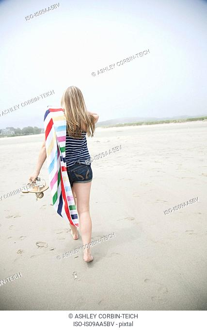 Young woman walking on beach with towel