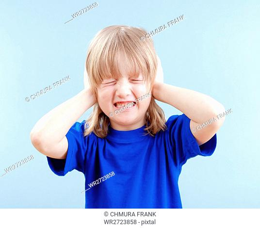 upset boy with long blond hair covering his ears as protection - isolated on blue