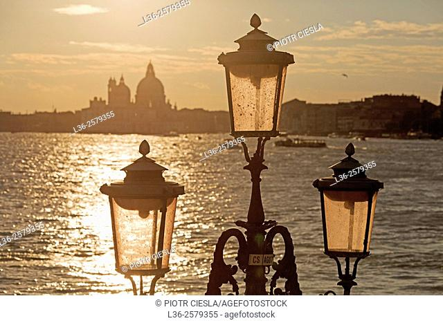 Venice. The silhouette of the Chiese Santa Maria della Salute and Venice lamps at sunset