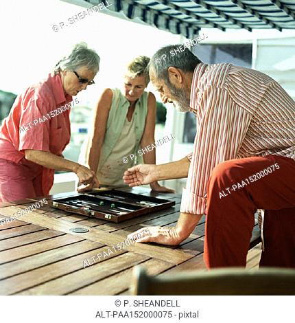 Three mature friends playing backgammon