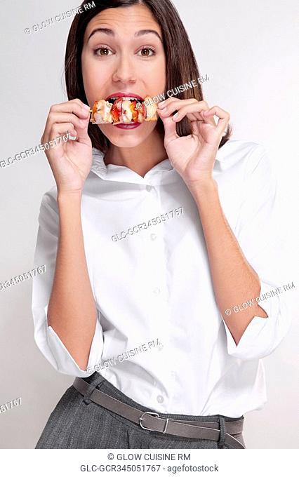 Portrait of a woman eating a shish kebab