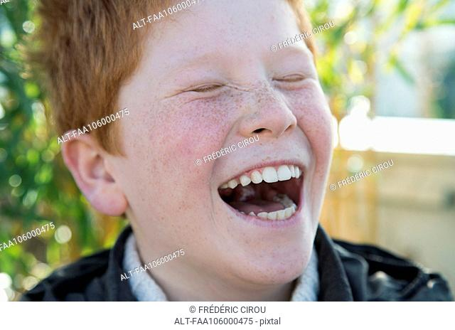 Boy laughing with eyes closed, portrait