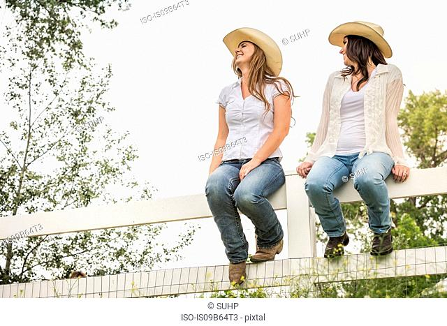 Young adult sisters in cowboy hats sitting on ranch fence, Bridger, Montana, USA