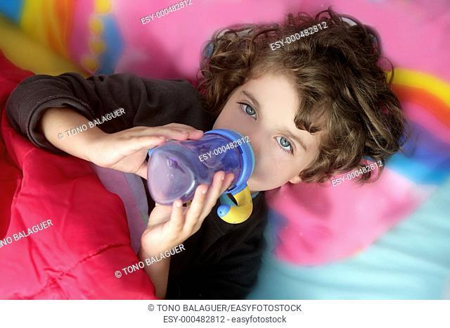 Adorable little brunette girl drinking bottle over pink pillow