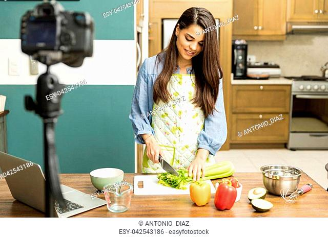 Portrait of a young woman cooking some food for her video blog at home