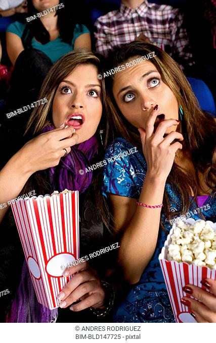 Hispanic friends enjoying popcorn in movie theater