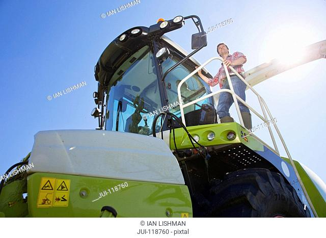Farmer climbing into forage harvester with tractor in background