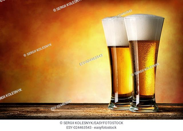 Two glasses of beer on a yellow background