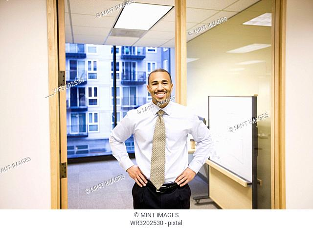 A portrait of a black businessman standing alone in his office space