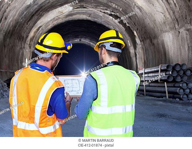 Workers reading blueprints in tunnel