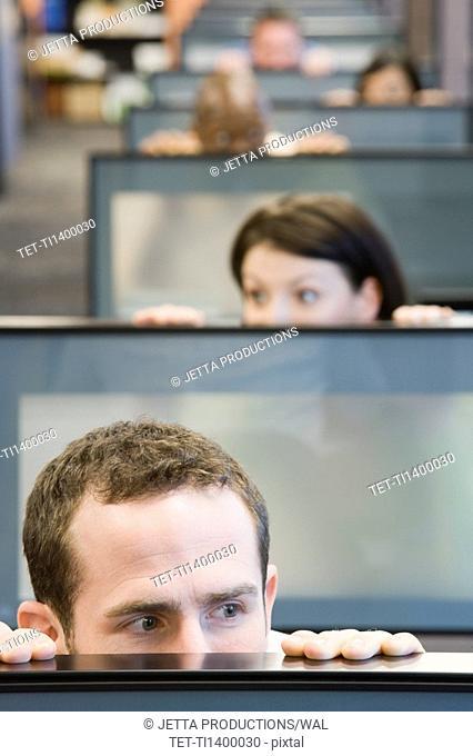 Businesspeople peeking over cubicle walls