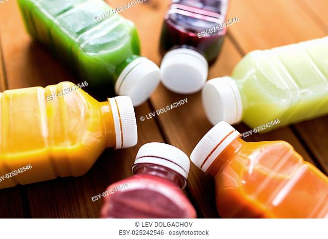 healthy eating, drinks, diet and detox concept - close up of plastic bottles with different fruit or vegetable juices on wooden table