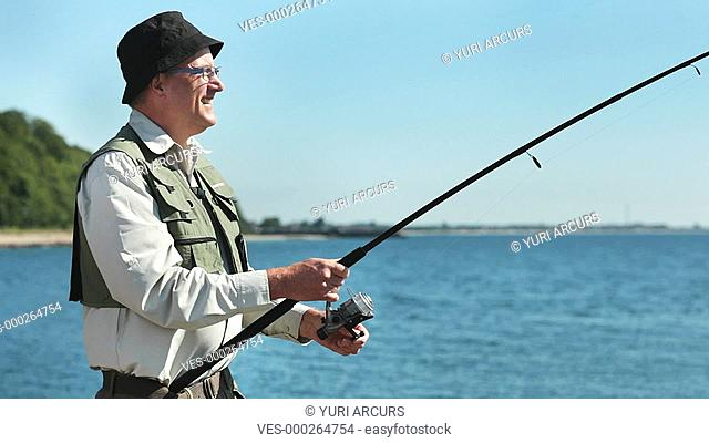 Senior man reeling in his catch on a bright day outdoors at a lake