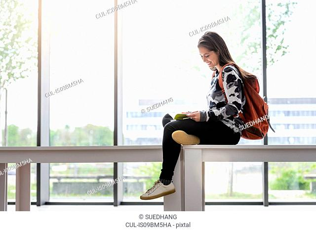 Female university student sitting on table reading a book in university lobby