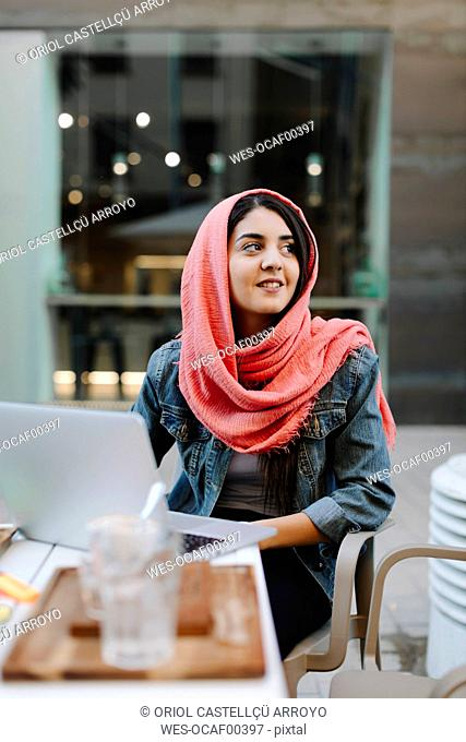 Smiling young woman with laptop wearing headscarf at a pavement cafe