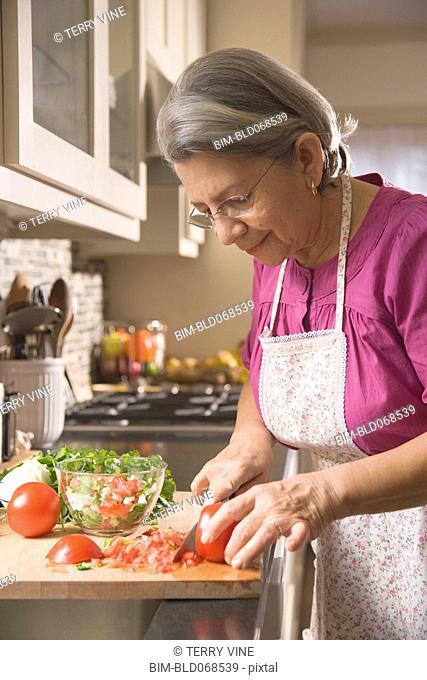 Hispanic woman cutting vegetables