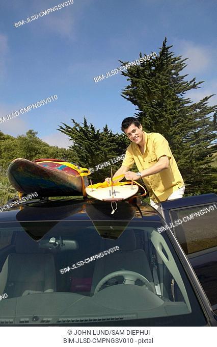 Man tying surfboard to car rack