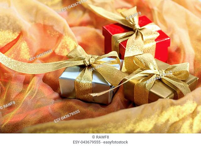 Gift boxes on a red gold red satin background