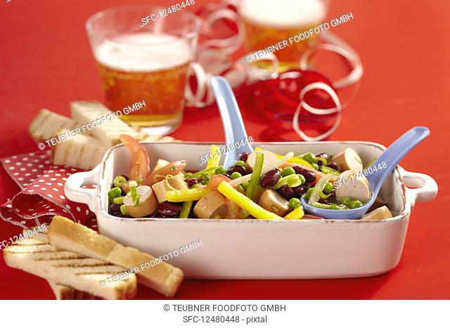 Colourful sausage salad with peppers, cucumber and kidney beans for carnival