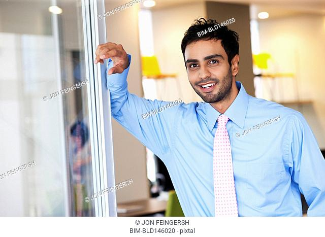 Businessman leaning against wall in office