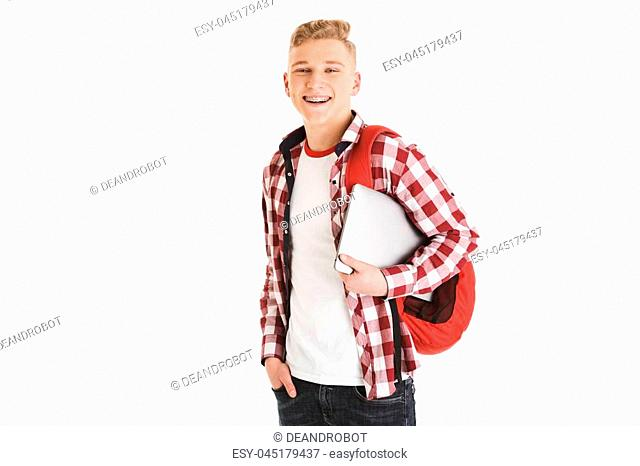 Portrait of attractive smart teenage boy wearing plaid shirt and braces smiling and looking on camera while holding silver laptop isolated over white background