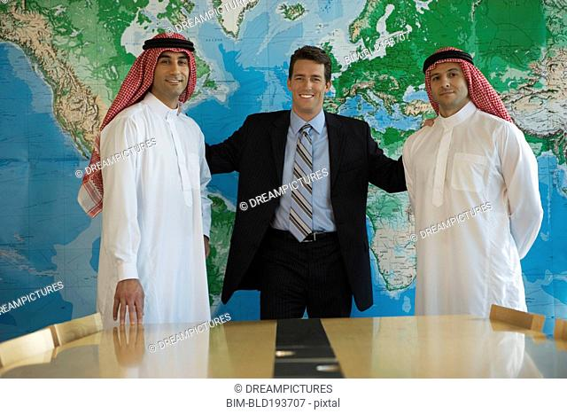 Middle Eastern businessman standing with men in traditional clothing