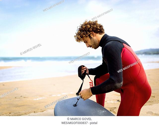 Spain, Asturias, Colunga, surfer preparing bodyboard on the beach