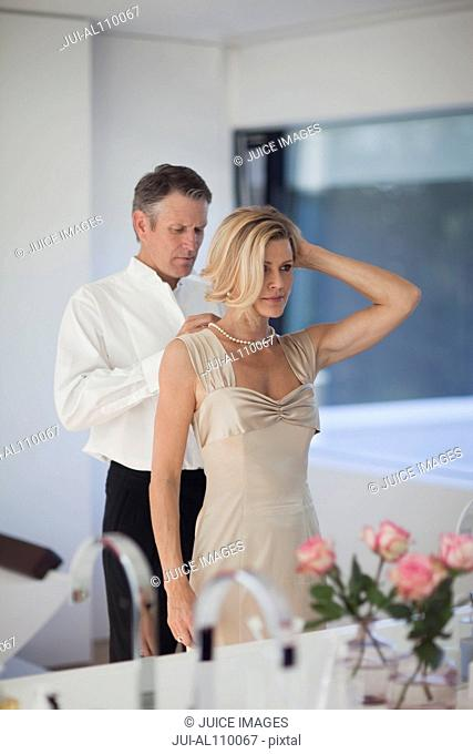 Mature man adjusting necklace of woman in mirror