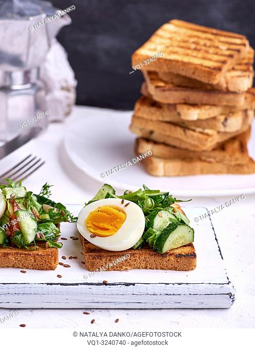 toasted square pieces of bread from white wheat flour with boiled egg, cucumber and green spinach leaves on a white wooden board, breakfast sandwich