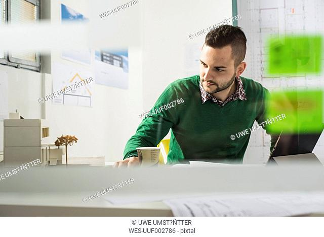 Young man at desk looking at architectural model