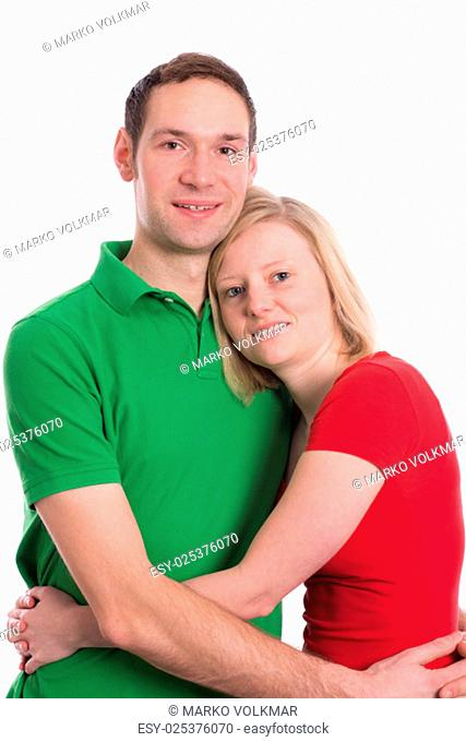 young couple in an embrace in front of white background