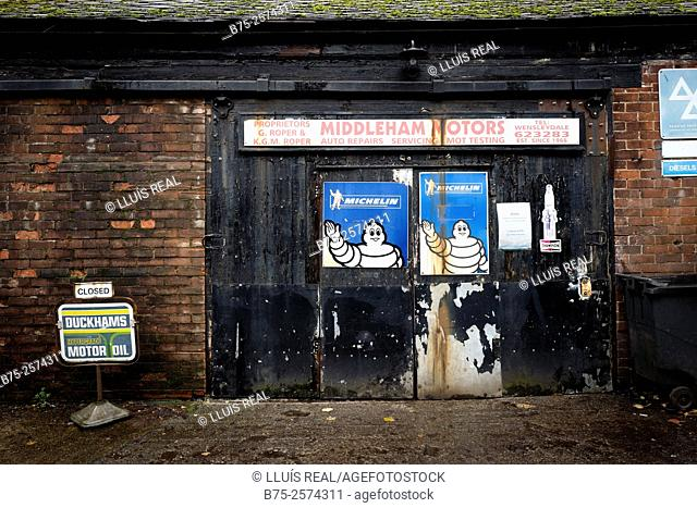 Facade and frontdoor of closed garage, with two posters of Michelin Bibendum. Middleham, Leyburn, Wensleydale, North Yorkshire DL8, Yorkshire Dales, England, UK
